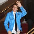 Dazu kombinierte er eine schlichte schwarze Hose und blau gemusterte Sneaker
