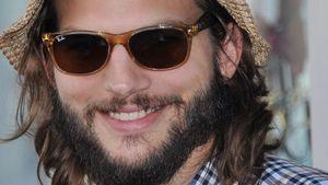 Ashton Kutcher lacht mit Brille und Hut