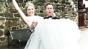 Caroline Fier im Hochzeitskleid wird von Dirk Borchardt hochgehoben