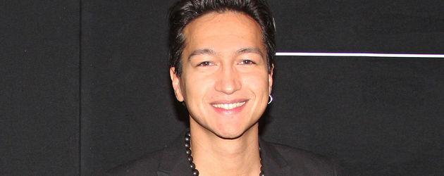 Anthony Thet im schwarzen Anzug