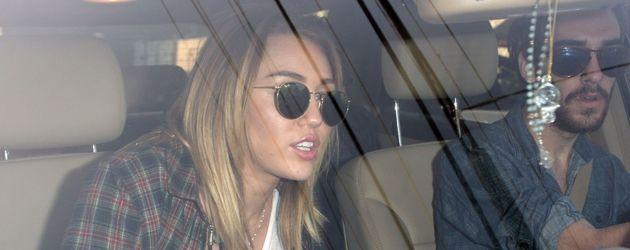 Miley Cyrus mit Sonnenbrille im Auto