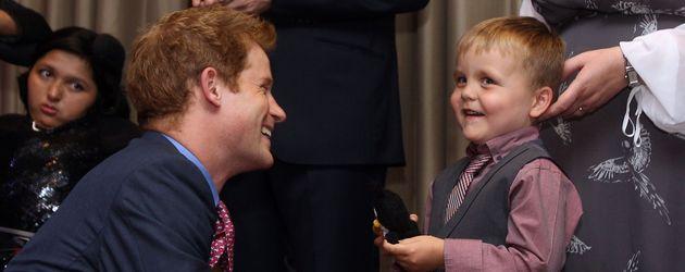 Prinz Harry kniet vor einem kleinen Jungen