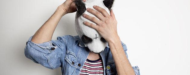 Rapper Cro fasst sich an die Panda-Maske