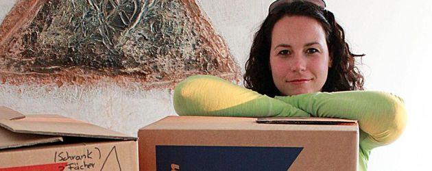 Ulrike Röseberg hinter einem Stapel Kisten