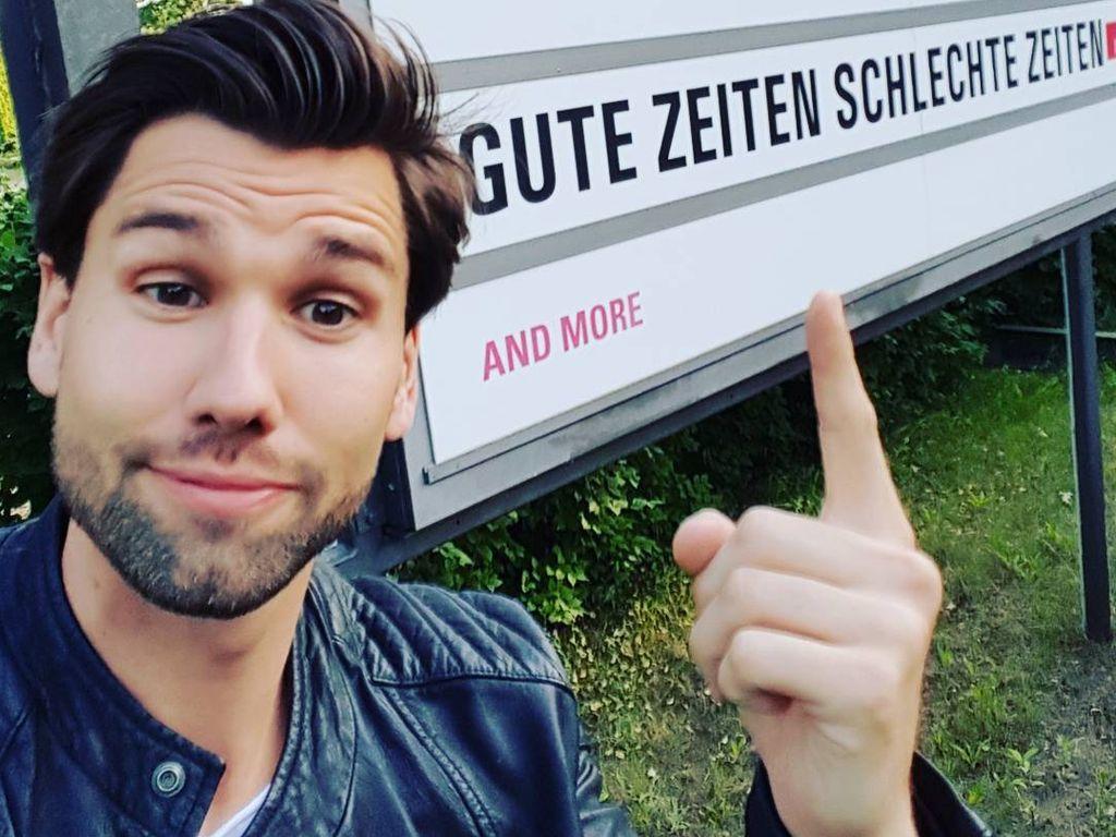 Alexander Keen steht in Babelsberg vor einem GZSZ-Schild