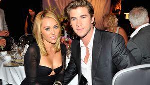Miley Cyrus und Liam Hemswort sitzen nebeneinander