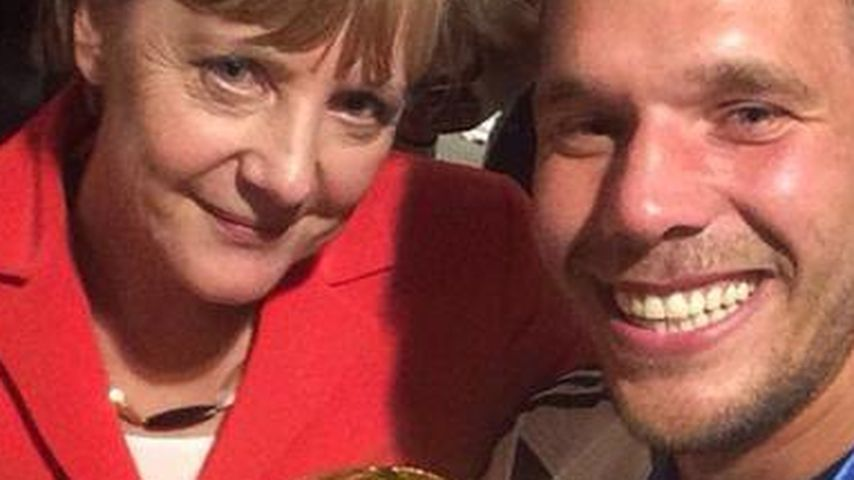 Lukas Podolski und Angela Merkel