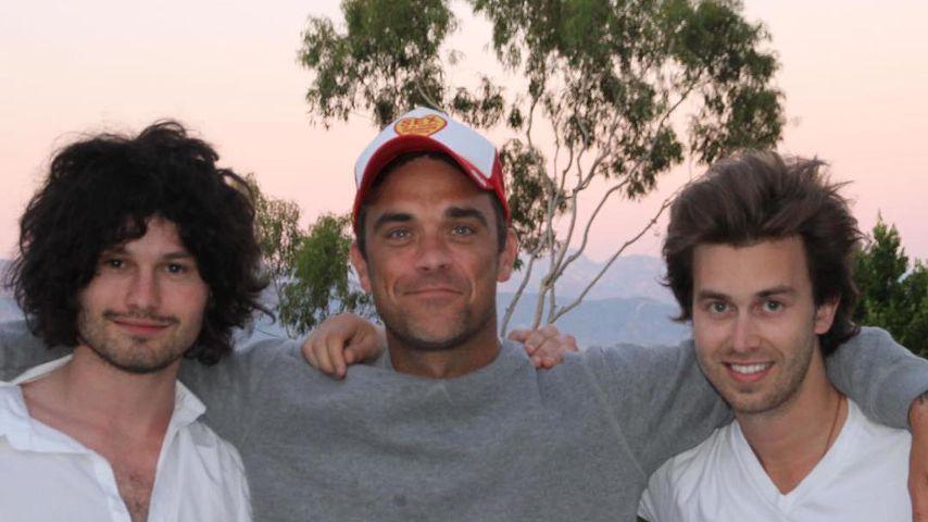 Robbie Williams (M.) mit seinen Songwritern Flynn Francis (l.) und Tim Metcalfe (r.)