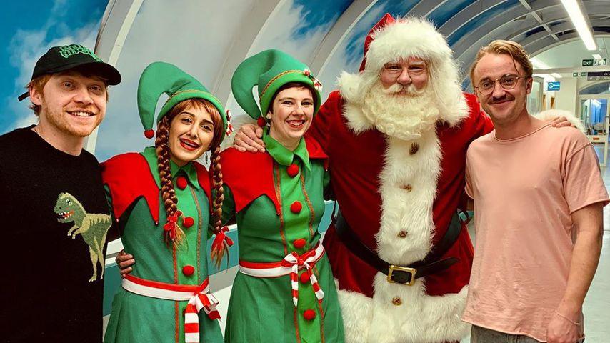 Rupert Grint (l.) und Tom Felton (r.) mit dem Weihnachtsmann und seinen Elfen