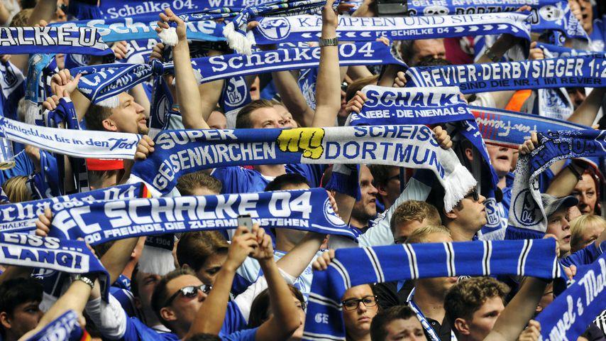 Schalke Fans in der Nordkurve mit Schals