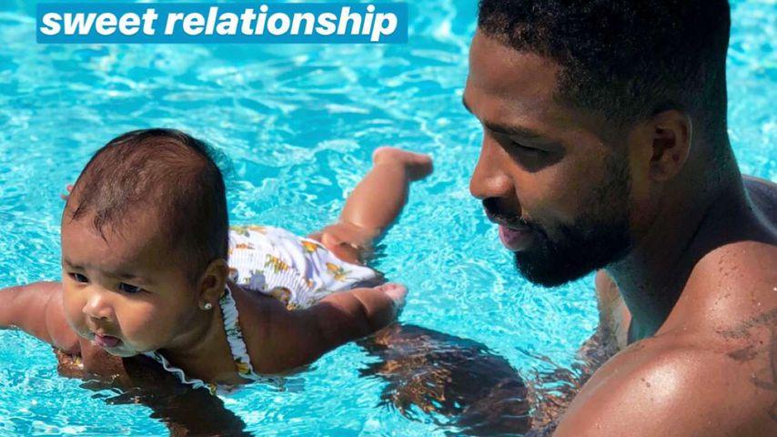In Papas starken Armen lernt Baby True Thompson schwimmen