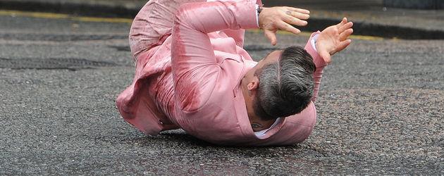Robbie Williams kugelt sich auf dem Boden