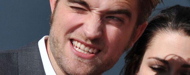 Robert Pattinson zieht eine Grimasse und Kristen Stewart hat ihre Augen geschlossen