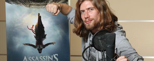 """Sarazar vor dem Filmplakat von """"Assassin's Creed"""""""